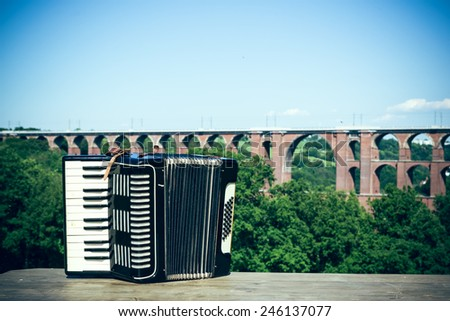 An accordion in front of the biggest brick bridge in the world - stock photo