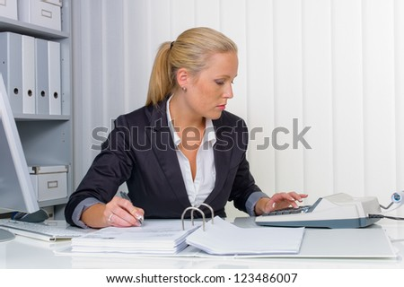 an accountant at work in the office with calculator - stock photo
