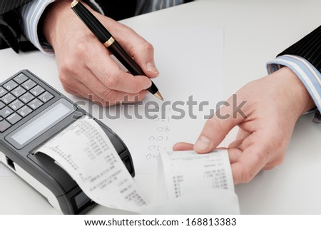 An accountant going through company's finances summing up the expenses - stock photo