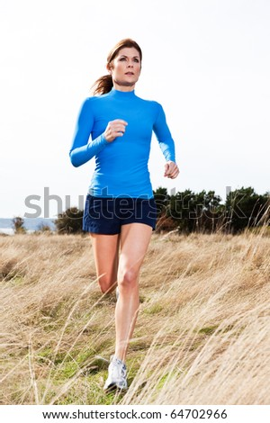 An active beautiful caucasian woman running outdoor in a park - stock photo
