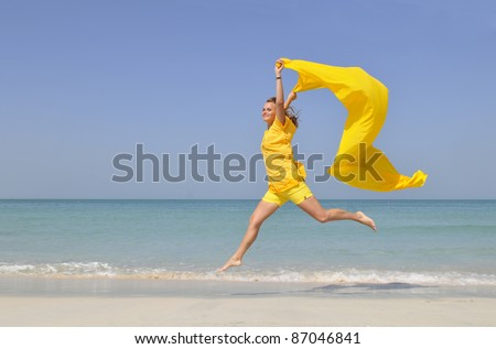 An active caucasian white fitness woman in yellow clothes running on the sand of the beach - stock photo