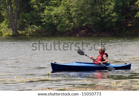 An active female senior citizen paddling around in a kayak. - stock photo