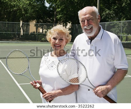 An active, happy senior couple on the tennis courts. - stock photo