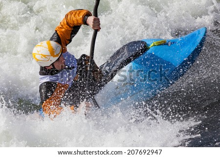 an active male kayaker rolling and surfing in rough water - stock photo
