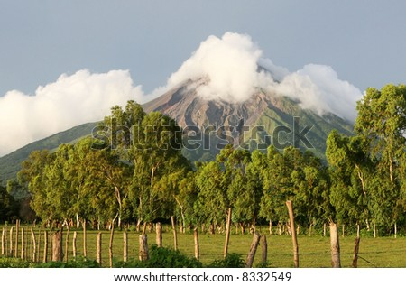 An active volcano looms  over rich, fertile fields below - stock photo