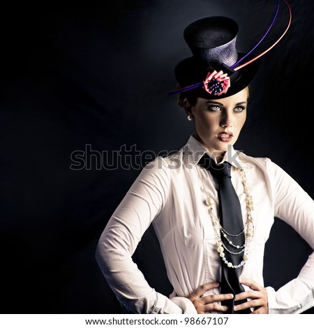 An actress dressed in typical vaudeville costume with a fascinator hat and tie performing on a darkened stage facing out of frame to an unseen audience - stock photo