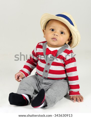 An adorable baby born sitting in his red and gray striped sweater, red bow tie and fedora.  On a gray background. - stock photo