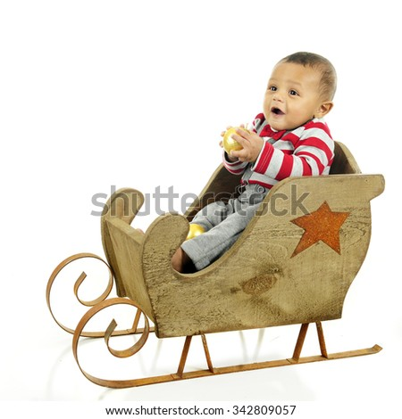 An adorable baby boy delightedly holding a gold Christmas bulb while sitting in a rustic sleigh waiting for a ride.  On a white background. - stock photo