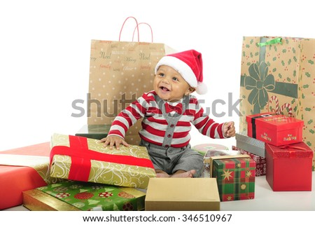 An adorable baby boy delightedly sitting in his Santa hat among many wrapped Christmas gifts.  On a white background. - stock photo