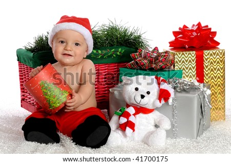 An adorable baby boy holding an opened Christmas box, surrounded  by other gifts.  Isolated on white. - stock photo