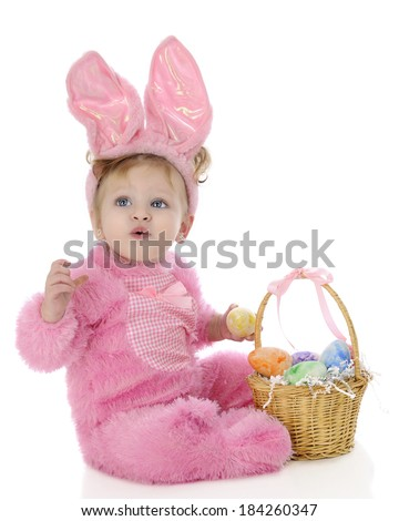 "An adorable baby girl ""Easter bunny"" attempting to whistle as she sits by her basket filled with colorful eggs.  On a white background. - stock photo"