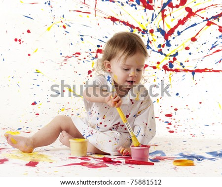 An adorable baby girl painting against a splattered paint background with plenty of space for your text. - stock photo