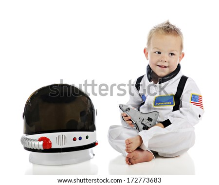 An adorable baby happily playing with a toy space shuttle while wearing his astronaut uniform and sitting by his space helmet.  On a white background. - stock photo