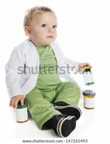 An adorable baby in lab coat and green scrubs sitting among pill bottles.  On a white background. - stock photo