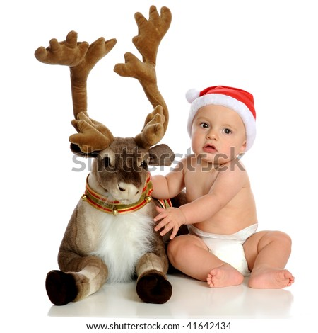 An adorable baby wearing Santa's hat posing with a plush reindeer. - stock photo