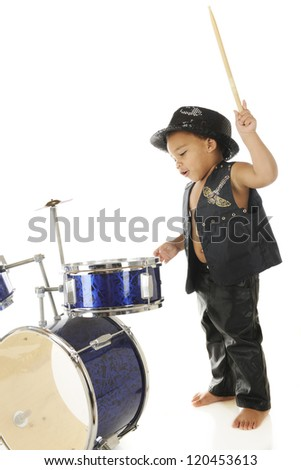 "An adorable, barefoot preschooler dressed as a rock star with a drum stick poised high over a drum set, ready to ""wham"" it.  On a white background. - stock photo"