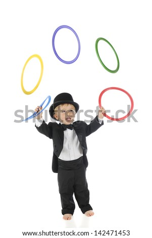 An adorable, barefoot toddler juggling colorful rings in his tuxedo and top hat.  Motion blur on the rings.  On a white background. - stock photo