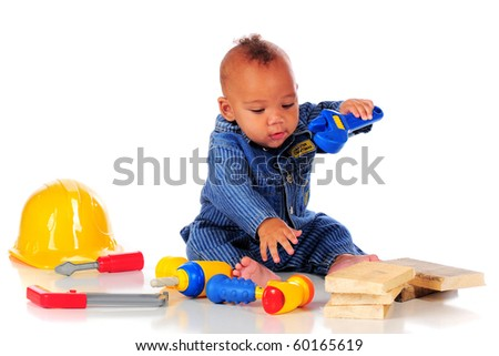 An adorable biracial baby in workman overalls eagerly playing with plastic tools.  isolated on white. - stock photo