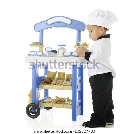 "An adorable biracial preschool ""baker"" counting the money he's made from his vendor stand.  The stand's signs are left blank for your text.  On a white background. - stock photo"