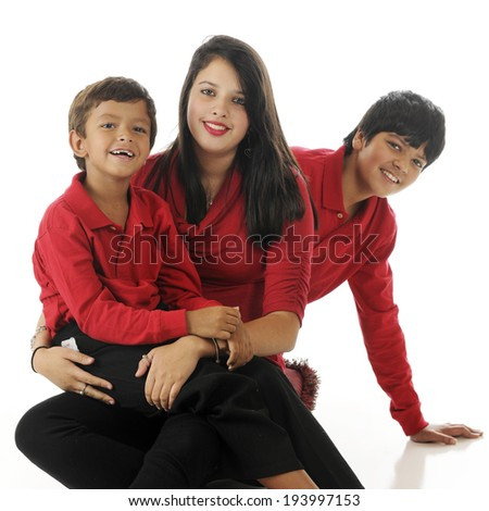 An adorable biracial preschooler sitting on his teen sister's lap.  His tween brother is peeking out from behind them both.  On a white background. - stock photo