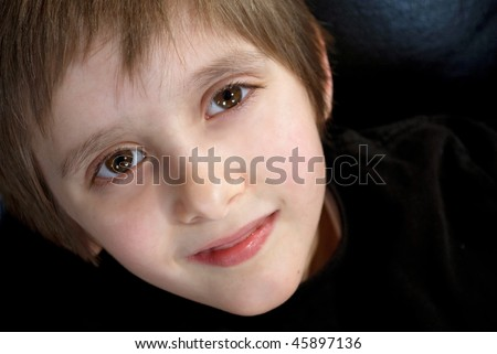 an adorable boy in black looking up at the camera with a slight smile - stock photo