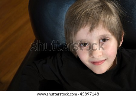 an adorable boy sitting in black leather chair looks up at camera - stock photo