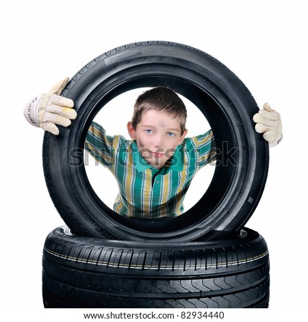 An adorable boy with gloves lifting a tire. Isolated on white. - stock photo
