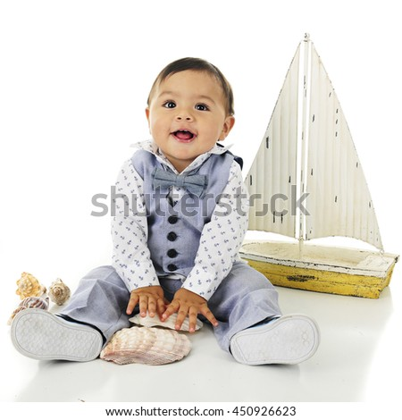An adorable, dressed up baby boy delighted with his sea shells.  A toy sailboat is nearby.  On a white background. - stock photo