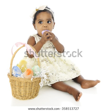An adorable, dressed up baby girl prepared to eat a whole egg from her Easter basket which sits by her side.  On a white background. - stock photo