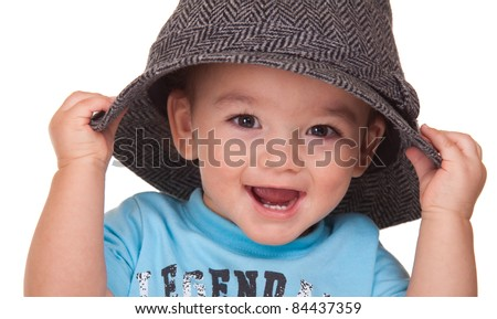 An adorable Hispanic baby is holding a hat.  Image is isolated on white with reflection. - stock photo