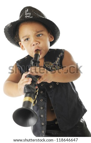 An adorable, intense preschool clarinetist in a sparkly fedora and black leather vest.  On a white background. - stock photo