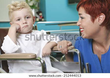 An adorable little boy in the wheelchair at the hospital with doctor - stock photo