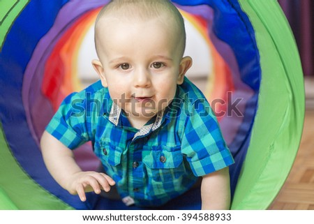 An Adorable little boy playing inside a toy tunnel - stock photo