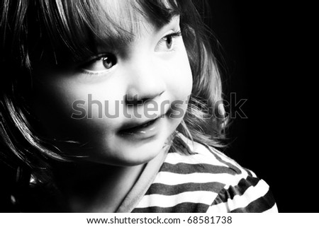 An adorable little girl looking to the light in front of a black background. Black and white. - stock photo
