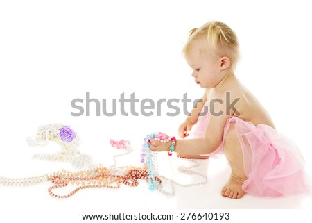 An adorable little girl squatting as she picks up a fistful of colorful pearls.  On a white background with plenty of space for your text above the multiple necklaces on the floor. - stock photo