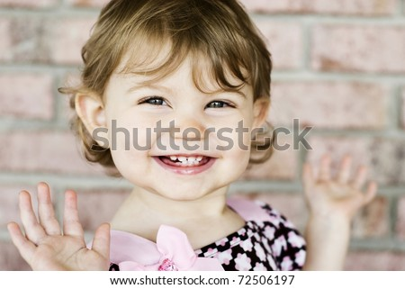 An adorable little girl with very expressive happy face, selective focus on face with blurred background - stock photo