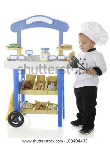 "An adorable preschool ""baker"" snitching cookies from his vendor cart.  On a white background.  Signs left blank for your text. - stock photo"