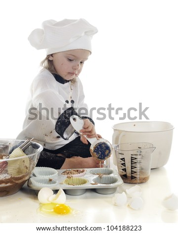 "An adorable preschool ""chef"" pouring her batter into a cup cake tin.  On a white background. - stock photo"