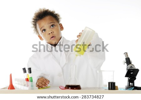 "An adorable preschool ""chemist"" looking up concerned as he's mixing oil into a dark water-based liquid.  On a white background.  - stock photo"