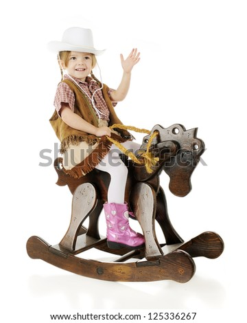 An adorable preschool cowgirl happily waving as she rides her wooden rocking horse.  On a white background. - stock photo
