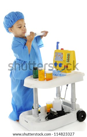 "An adorable preschool ""doctor"" in blue scrubs checking the measurements on a large syringe as he stands by an emergency cart.  On a white background. - stock photo"