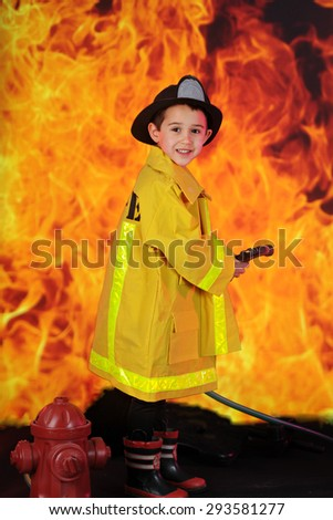 "An adorable preschool ""fireman"" ready to douse raging flames with his hose. - stock photo"