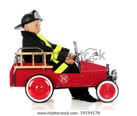 An adorable preschool fireman spacing out in his fire truck.  Isolated on white. - stock photo