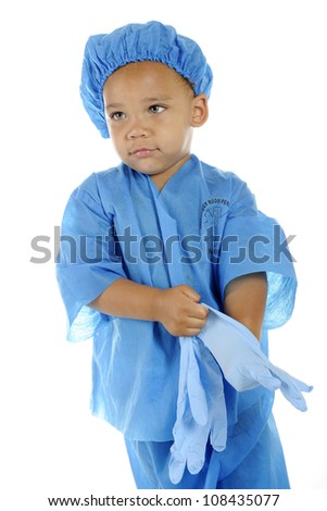 "An adorable preschool ""surgeon"" in blue scrubs donning his surgical gloves.  On a white background. - stock photo"