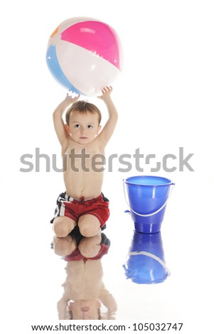 """An adorable preschooler playing with a sand pail and colorful beach ball by the """"water's edge,""""  with a watery reflection.  On a white background. - stock photo"""