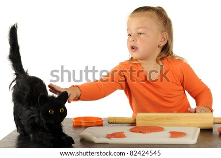 An adorable preschooler playing with modeling dough cautiously reaching out to touch a scary black cat. - stock photo