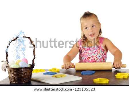 An adorable preschooler rolling out kiddie dough for cutting out with Easter-shaped cookie cutters. - stock photo