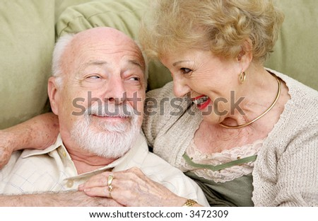 An adorable senior couple laughing together at home.  It's obvious they still have chemistry together. - stock photo