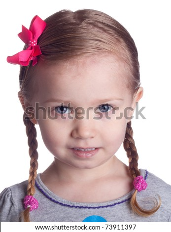 An adorable shy girl with pig tails and braids.  She has a pink bow in her hair. - stock photo