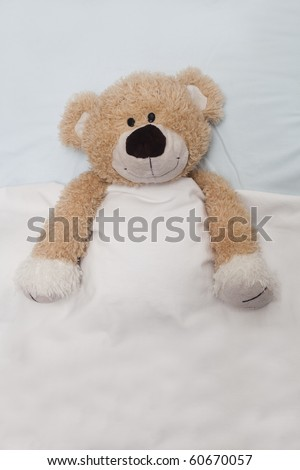 An adorable teddy bear laying in bed, under the sheets. - stock photo